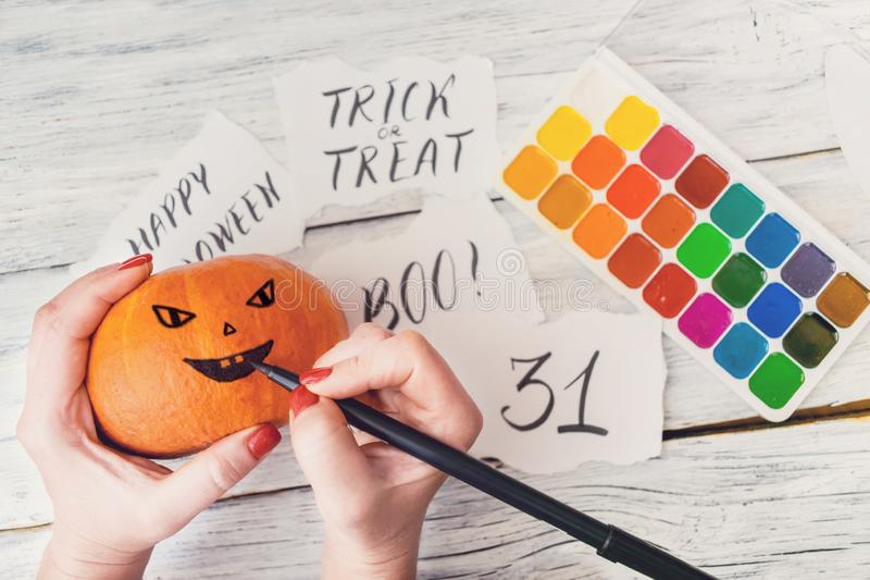Fall Halloween crafts. Female hands draw Jack O' Lanterns on o royalty free stock photography