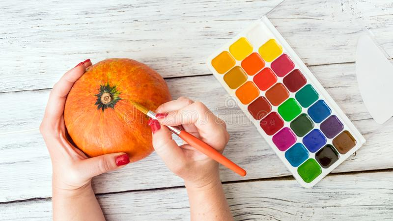 Fall Halloween crafts. Female hands with orange decorative pumpkin and bright paint with brush on white wooden background. Jack O royalty free stock image