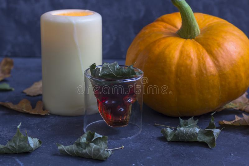 Fall Halloween pumpkins, candle, glass in the form of a skull on a dark background stock image