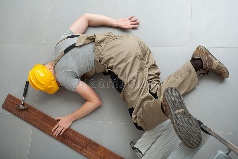 Fall from a ladder. Manual worker dressed in work clothes lying unconscious on the grey floor royalty free stock photos