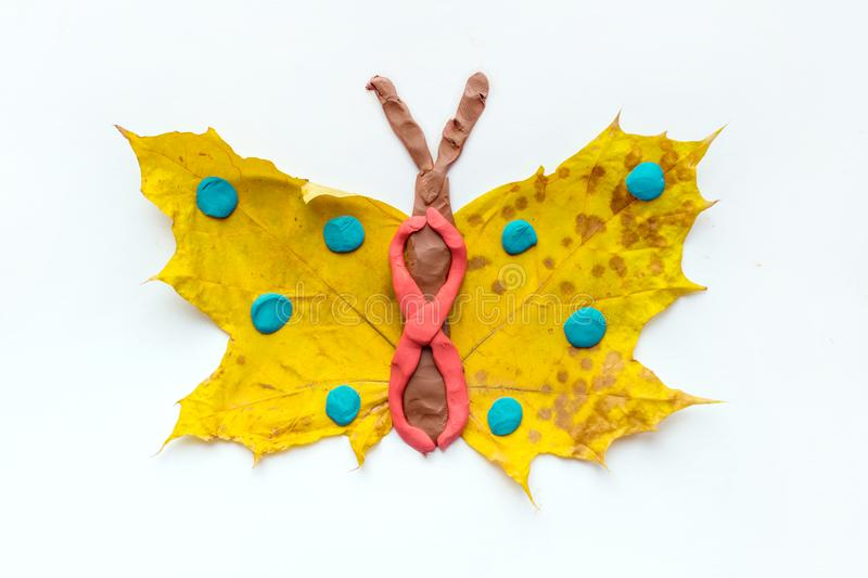 Fall Leaf Crafts for Kids. Craft handmade butterfly from dry yellow leaves and red, brown and blue plasticine, modeling clay. Ide stock photo