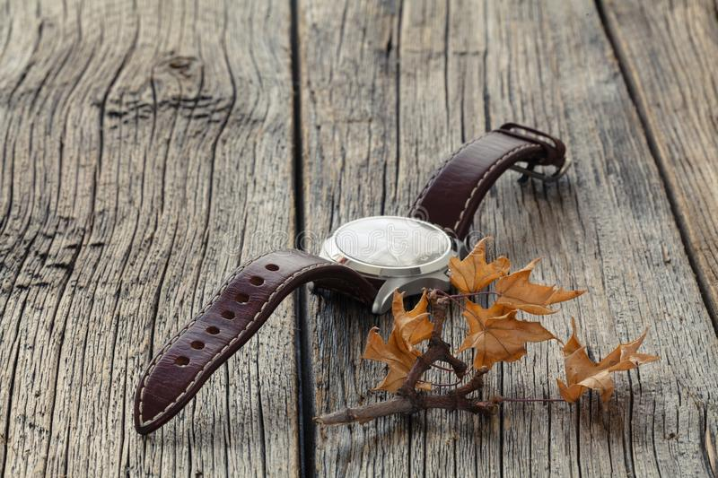 Fall leaf and watch. Seasoning Daylight savings time concept stock images