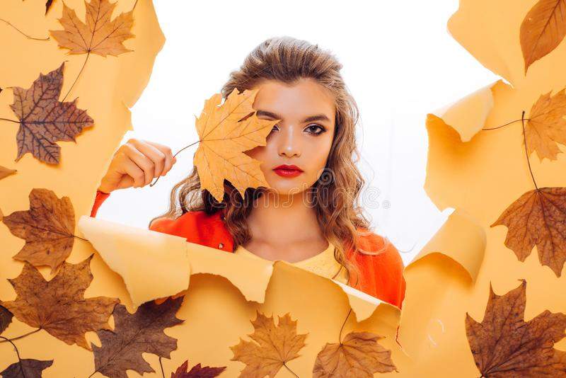 Fall look. Makeup girl peek through torn paper. Pretty girl cover face with autumn leaf. Young woman look out of hole. Fashion model with decorative fall royalty free stock photography