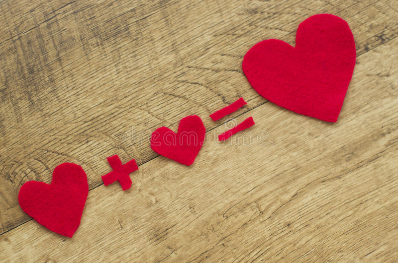 Fall in love. Equation with hearts on wooden background royalty free stock photo