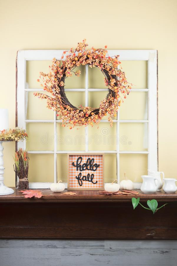 Fall mantel decor - light and bright style. Autumn decorations on the mantel - hello fall sign and vintage window frame stock images