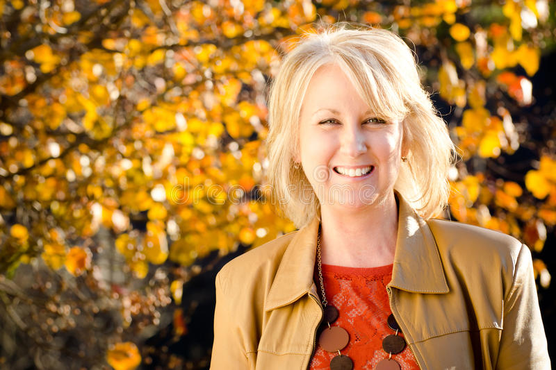 Fall portrait of happy middle-aged woman. Fall portrait of happy middle-aged blonde woman royalty free stock photo