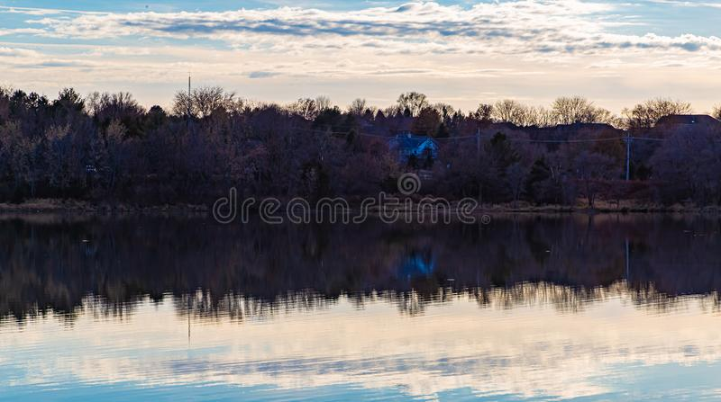 Fall reflections; when the leaves fall, you see a lot more on the shoreline. The tree branches, houses, roads, sheds are visible. Fall autumn reflections; when royalty free stock images