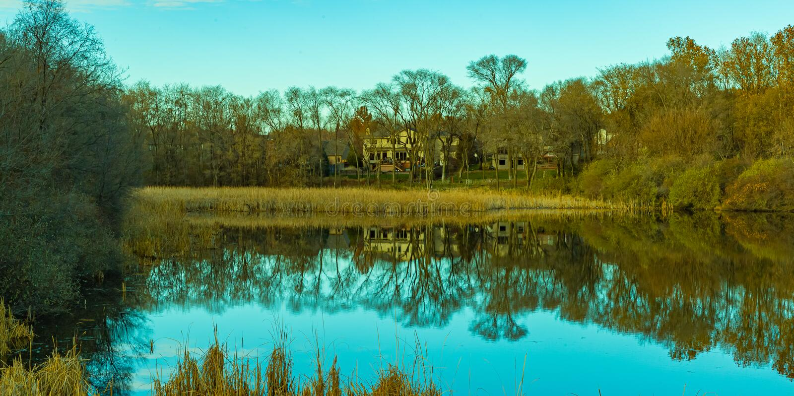 Fall reflections; when the leaves fall, you see a lot more on the shoreline. The tree branches, houses, roads, sheds are visible. Fall autumn reflections; when royalty free stock photo