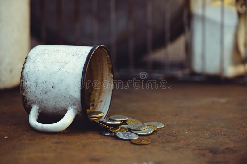 The fall of the Russian ruble, poverty and poverty scattered coins in the old mug on a rusty background, sanctions royalty free stock image