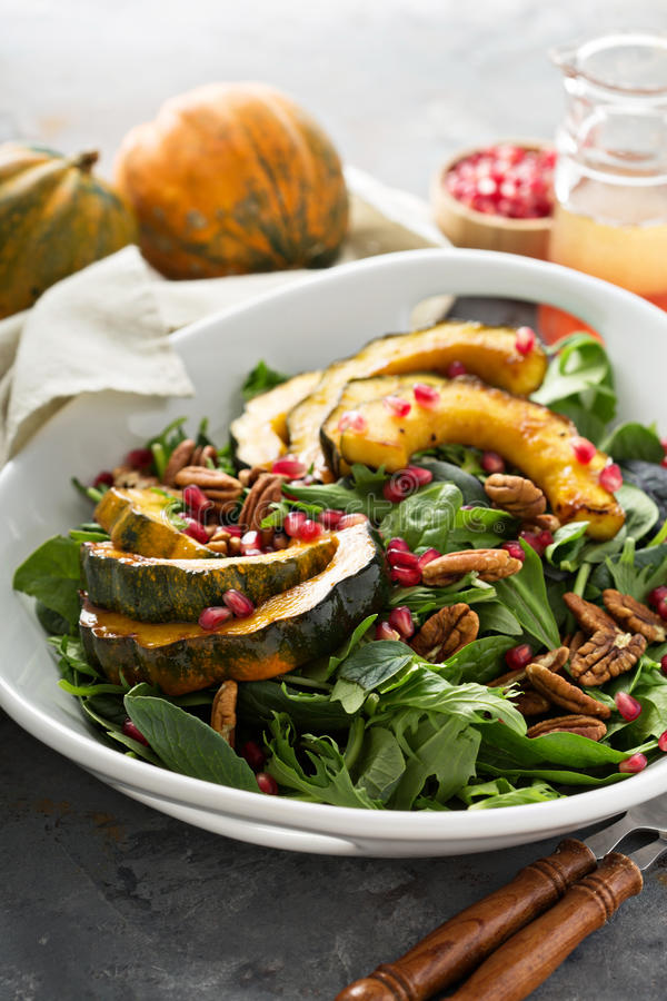 Fall salad with greens and acorn squash. Fall salad with greens, nuts, pomegranate seeds and roasted acorn squash royalty free stock photography