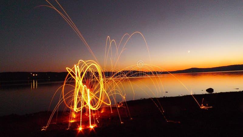 Fall-Schattenbild durch den See mit Feuer-Licht-Malerei stockbilder