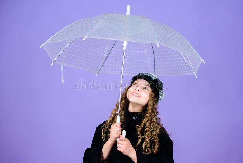 Fall season. Enjoy rain concept. Kids fashion trend. Love rainy days. Kid girl happy hold transparent umbrella. Enjoy. Rainy weather with proper garments stock photography