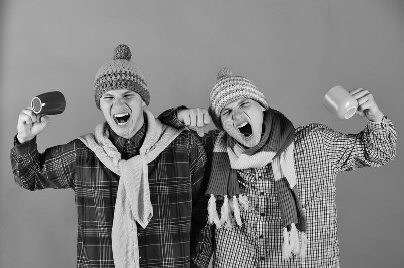 Fall season and family cheer concept. Siblings enjoy coffee or tea. Twin brothers in warm hats stock photo
