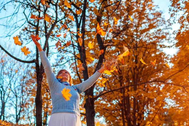 Fall season. Woman throwing leaves in autumn forest. Senior woman having fun outdoors royalty free stock photo