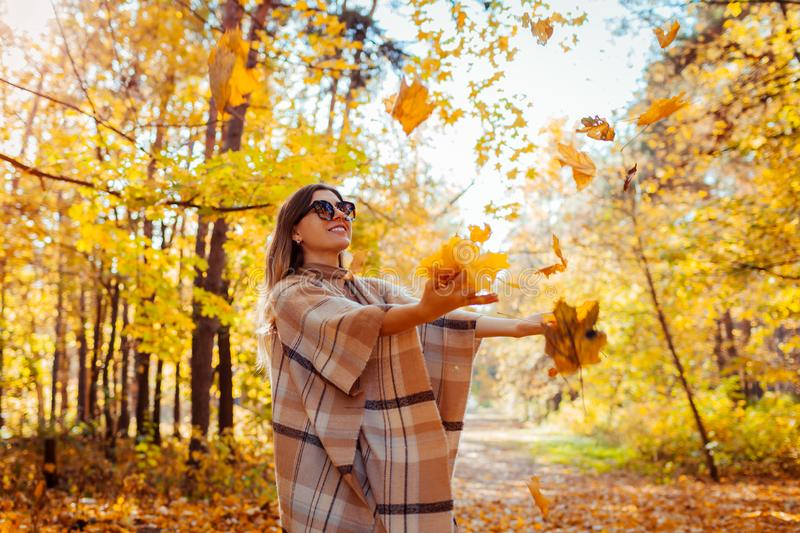 Fall season. Woman throwing leaves in autumn forest. Young woman having fun outdoors royalty free stock images