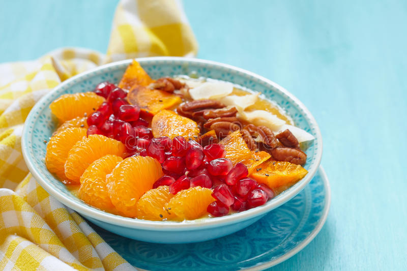Fall Smoothie in a bowl. Smoothie with clementine, persimmon, pomegranate and pecan royalty free stock photography
