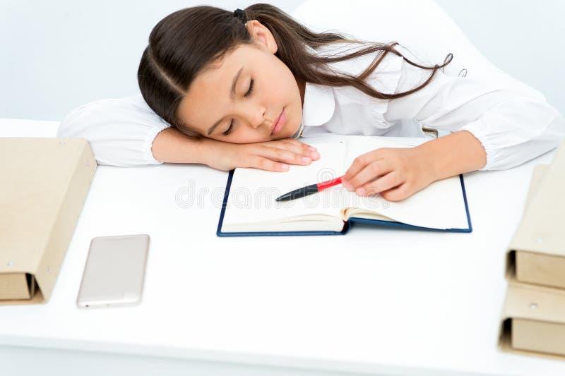 Fall sovande på kurs Flickabarnet faller sovande medan bakgrund för läseboktabellvit Skolflicka som tröttas av att studera royaltyfri foto