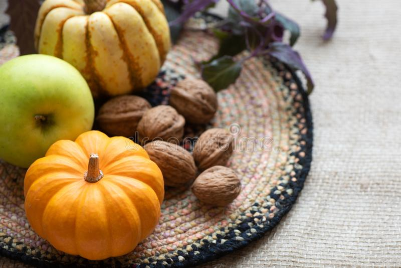 Fall Still Life with Mini Pumpkin, green apple,walnuts and delicata sweet dumpling squash.  A horizontal with copy space in natura stock images