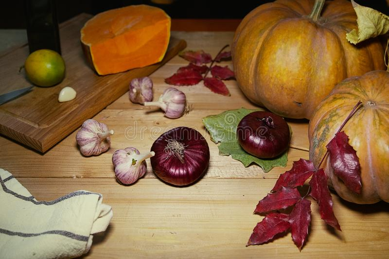 Fall still life with pumpkin,garlic,red onions,lime,cutting board and kitchen towel on rustic wooden table. royalty free stock photo