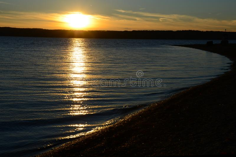 Fall sunset on Cayuga Lake shoreline in NYS. Calm, peaceful serene water of Cayuga Lake at sunset during Autumn in the FingerLakes stock images