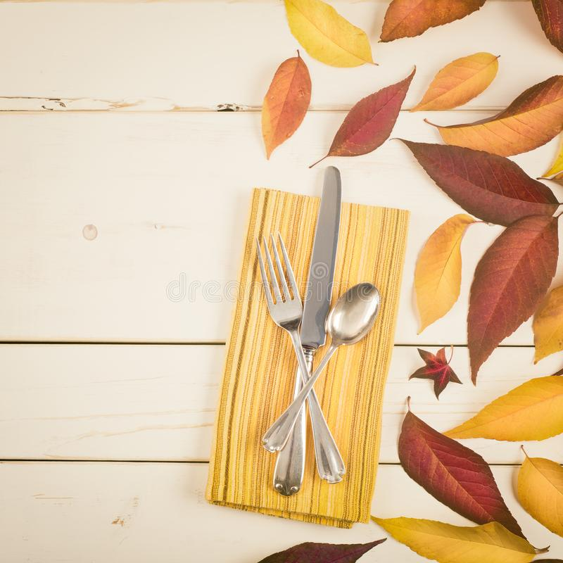 Fall Table Place Setting Invite Card with Brown and Gold Leaves, Silverware, and Napkin Flat Lay on White Shiplap boards backgrou royalty free stock image