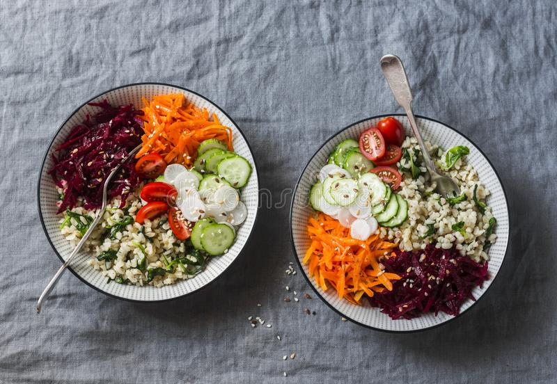 Fall vegetarian buddha bowl. Bulgur, spinach, beets, carrots, cucumbers, tomatoes, daikon - balanced healthy eating lunch. On a gr stock image