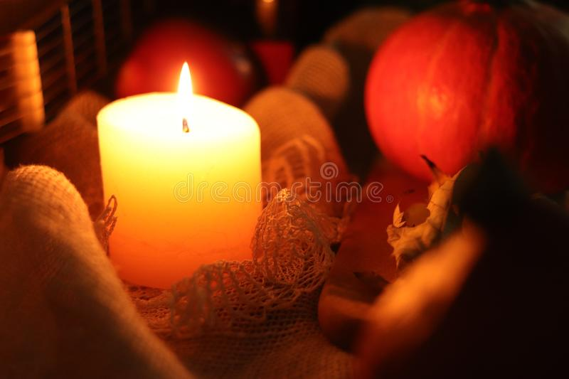 Fall warmth still life. Soft candle light with pumpkin and leaf on lace sackcloth background stock images