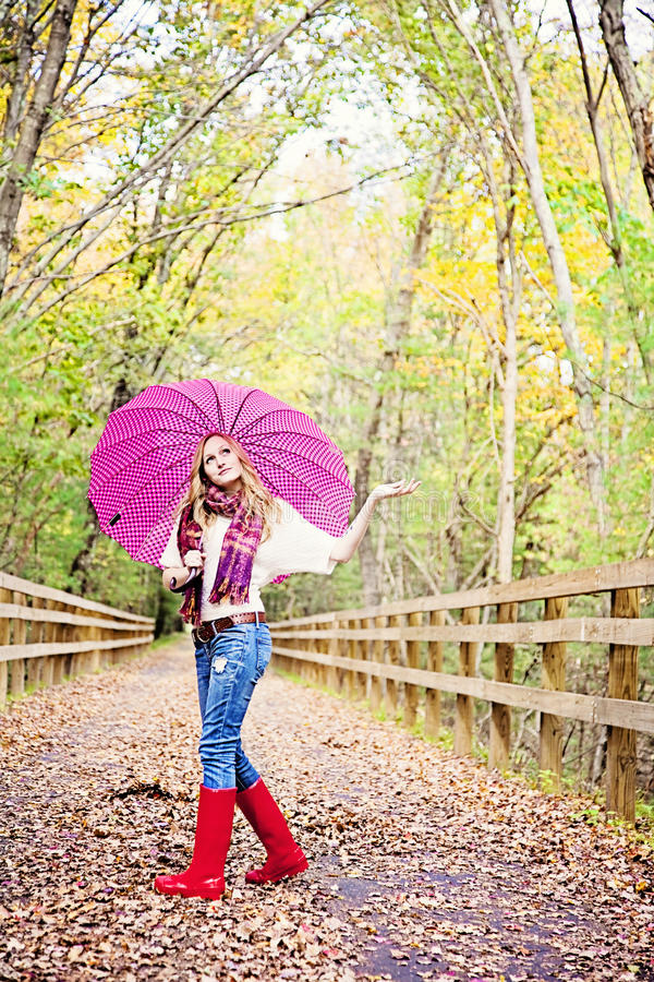 Fall weather. A pretty young woman under an umbrella walking on a path in autumn looking up
