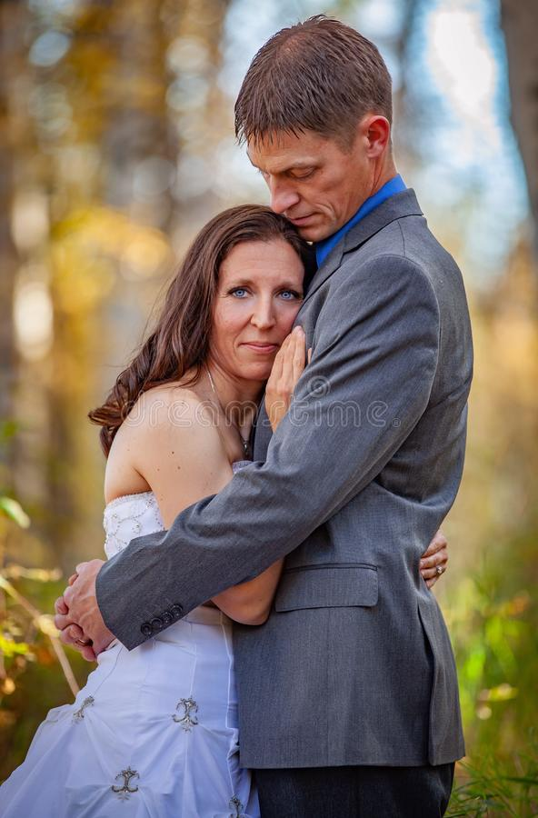Bride and groom in outdoors during fall stock photo