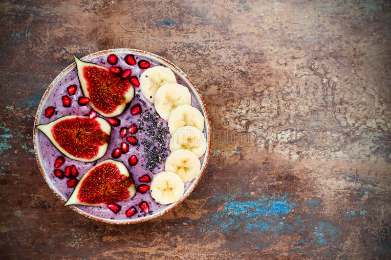 Fall and winter breakfast set. Acai superfoods smoothies bowl with chia seeds, pomegranate, banana, fresh figs, hazelnut butter. stock image