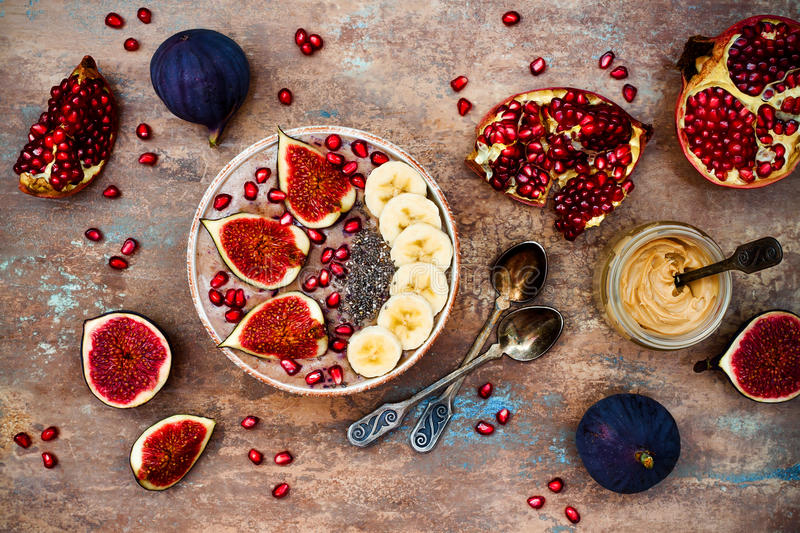 Fall and winter breakfast set. Acai superfoods smoothies bowl with chia seeds, pomegranate, banana, fresh figs, hazelnut butter. Healthy fall and winter royalty free stock images