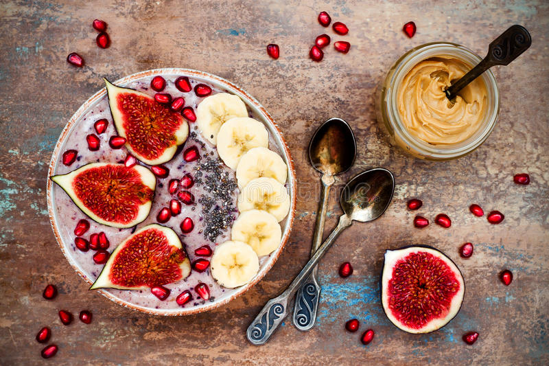 Fall and winter breakfast set. Acai superfoods smoothies bowl with chia seeds, pomegranate, banana, fresh figs, hazelnut butter. royalty free stock photography