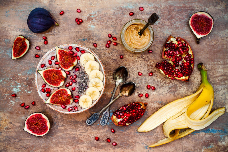 Fall and winter breakfast set. Acai superfoods smoothies bowl with chia seeds, pomegranate, banana, fresh figs, hazelnut butter. Healthy fall and winter stock photos