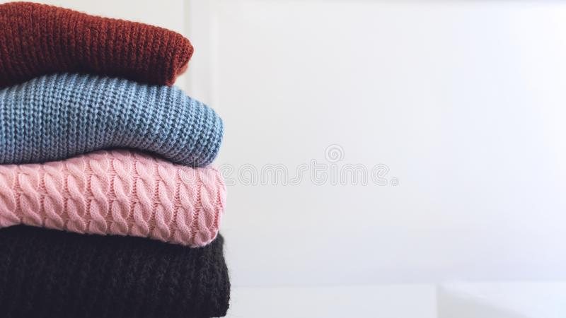 Fall winter fashion trends. Stack of cozy knitted sweaters in retail shop, store. Fashion shopping sale background with copy space stock images