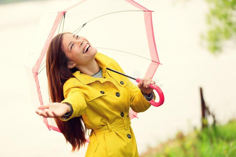 Fall woman happy after rain walking umbrella. Fall woman happy after rain walking with umbrella. Female model looking up at clearing sky joyful on rainy Autumn stock images