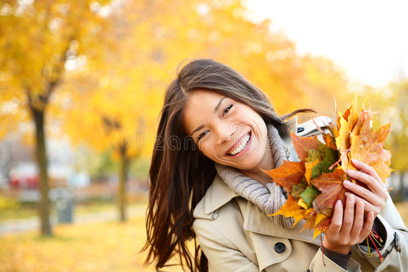 Fall woman playing with leaves. Autumn girl playing in city park. Fall woman portrait of happy lovely and beautiful mixed race Asian Caucasian young woman in
