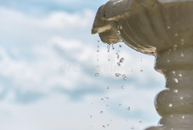 Fallande droppar av vatten i springbrunnen och att frysa, blå himmel i bakgrunden royaltyfria bilder