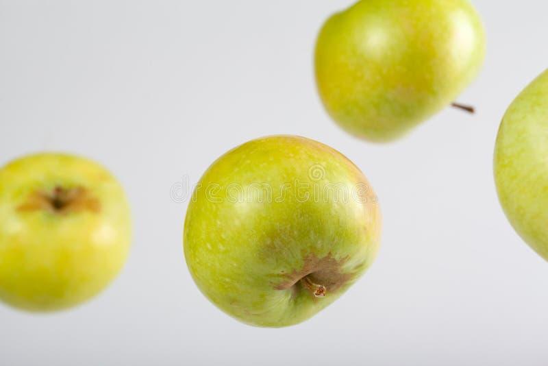 Fallande gröna äpplen arkivfoto