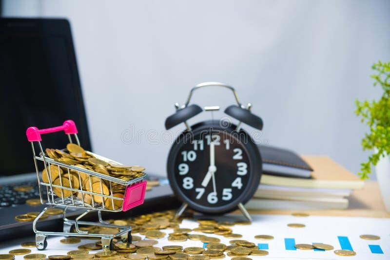 Fallande guld- mynt i shoppingvagn eller supermarketsp?rvagn p? den arbetande tabellen med n?dv?ndiga hj?lpmedel f?r kontorstillf royaltyfri bild