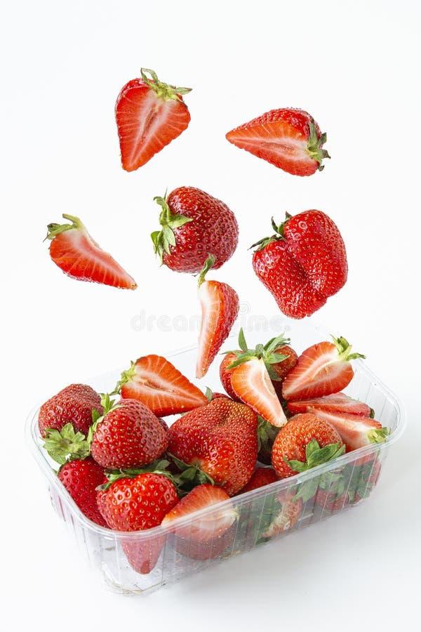 Fallande jordgubbar i en genomskinlig plast- packe levitation Sommarbärsäsong Isolerade objekt p? vit bakgrund royaltyfri bild