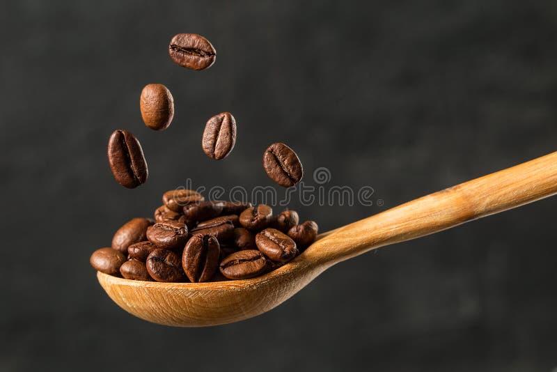 Fallande kaffeböna för makro på grå bakgrund royaltyfria foton