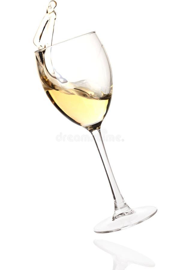 fallande plaska vit wine för exponeringsglas arkivbild
