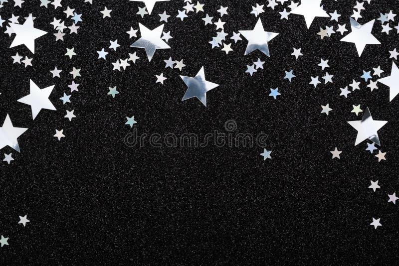 Fallande silverstjärnakonfetti på svart festligt glöda för bakgrund mousserar ramen arkivbild