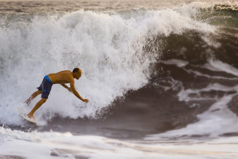Fallande surfare på blå havvåg i Bali royaltyfri foto
