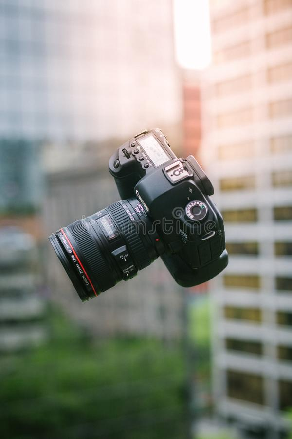 Fallande yrkesmässig kamera som fångas i luften med suddig arkitektur i bakgrunden royaltyfri foto