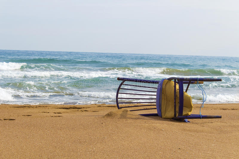 Falled old chair in sand at seaside royalty free stock photography