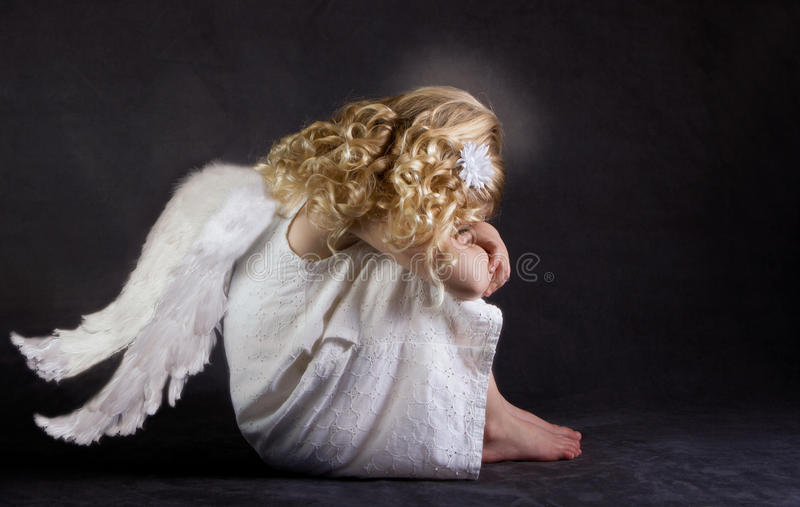 A fallen angel. Or child angel who is sad stock images