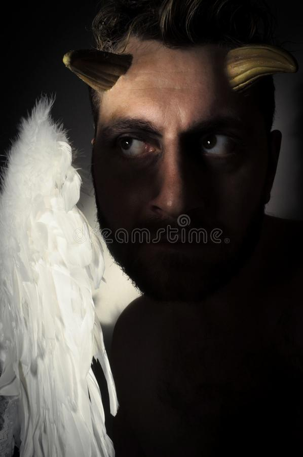 Fallen Angel Demon. Fallen angel satan with feathered wings and moody lighting royalty free stock photo