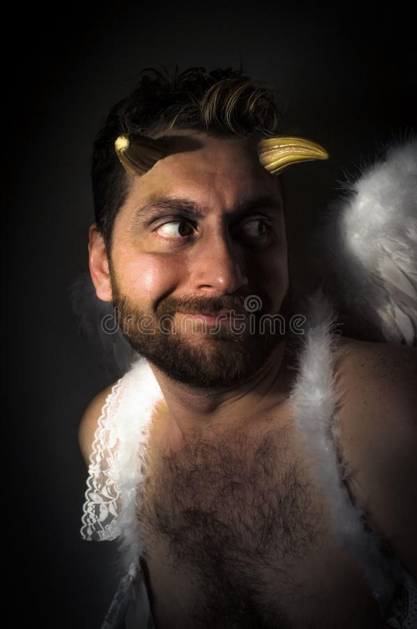 Fallen Angel Demon. Fallen angel satan with feathered wings and moody lighting royalty free stock image