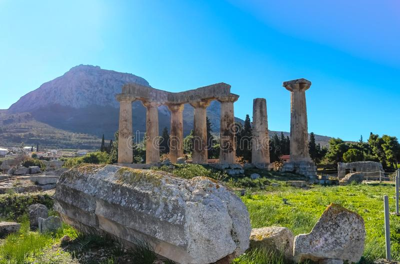 Fallen broken pillar laying on ground in front of the ruins of the Temple of Apollo at Corith Greece with the acropolis of Acroco stock photos